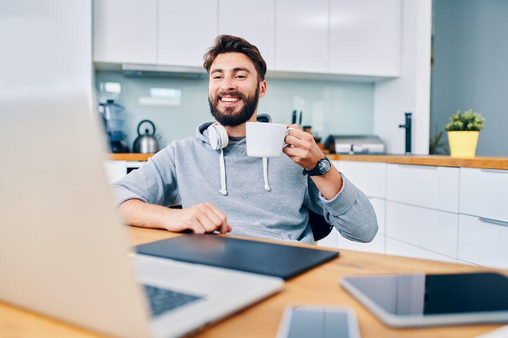 Joyful young web developer drinking coffee while taking break from work in home office